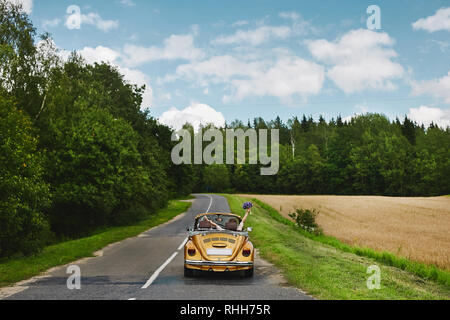 Golden retro cabriolet with a couple of just married, on the empty road between the field and the forest - Stock Photo