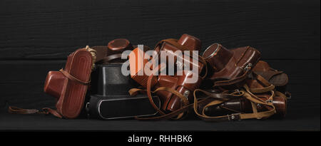 Heap of 35mm old cameras in leather covers, black background. Collection and auctions