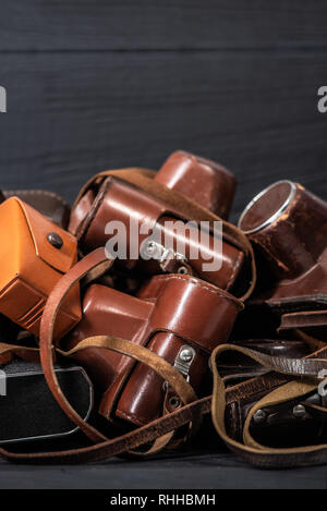 Heap of 35mm retro cameras in leather covers on black