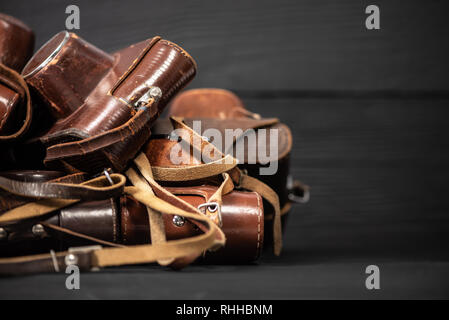 Heap of 35mm analog cameras in leather covers on black background
