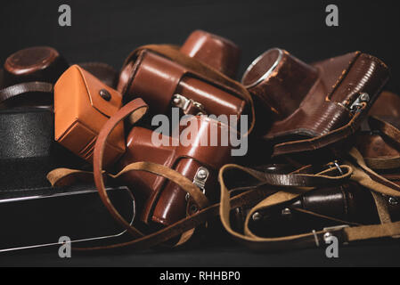 Heap of 35mm vintage cameras in leather covers. Collecting