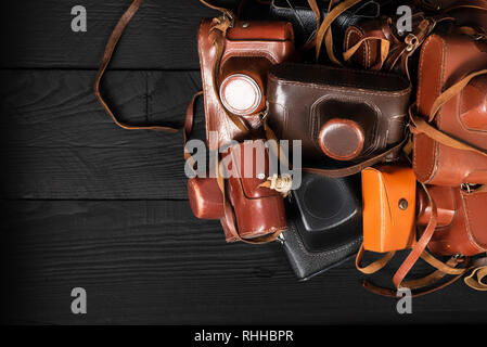 Heap of 35mm retro cameras in leather covers on black, top view. Collection of old things and antiques, auctions