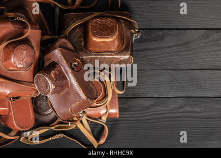 Drohobych, Ukraine - 02 February, 2019: Heap of 35mm retro cameras in leather covers on black, top view