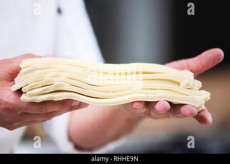 Pastry chef showing dough sheets ready to be rolled to produce croissant . - Stock Photo