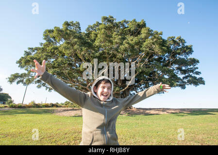 Young boy with outstretched arms in front of a large fig tree, Wollongbar, NSW, Australia - Stock Photo
