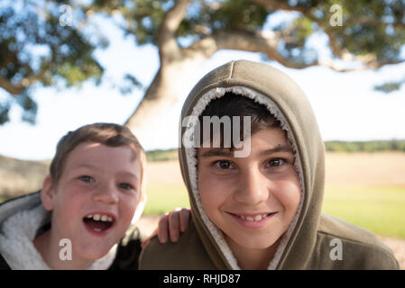 Two young boys under a tree, Wollongbar, New South Wales, Australia - Stock Photo