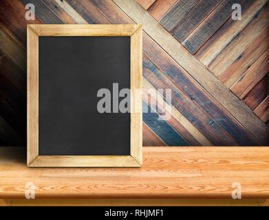 Blackboard on plank wooden table top at diagonal tropical wood wall,Template mock up for adding your design and leave space beside frame for adding mo - Stock Photo