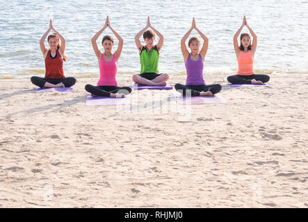 Yoga class at sea beach in evening ,Group of people doing tree poses with clam relax emotion at beach,Meditation pose,Wellness and Healthy balance lif - Stock Photo