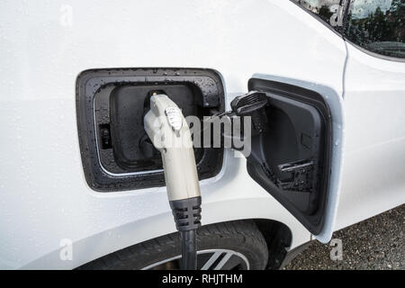 Electric vehicle with the power plug connected to the car - Stock Photo