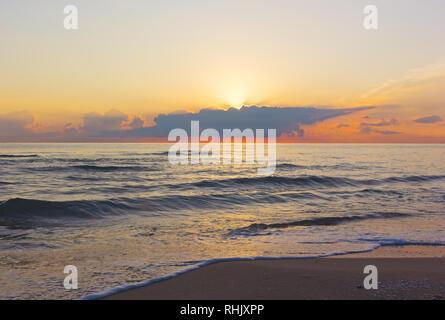 Dreamy sunrise over the sea. Sun arises from the clouds over Mediterranean Sea in Valencia region of Spain. - Stock Photo
