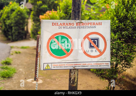 BALI, INDONESIA - 21 May, 2018: A protest sign on a wall in Indonesian objecting to Uber and Grab taxi drivers reads 'Uber and Grab Taxis No Entry' in - Stock Photo