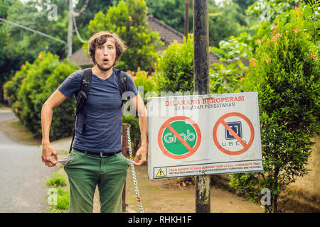 BALI, INDONESIA - 21 May, 2018: Young man looks at protest sign on a wall in Indonesian objecting to Uber and Grab taxi drivers reads 'Uber and Grab - Stock Photo