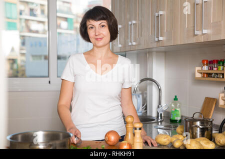 Portrait of happy brunette woman among  kitchenware in kitchen - Stock Photo