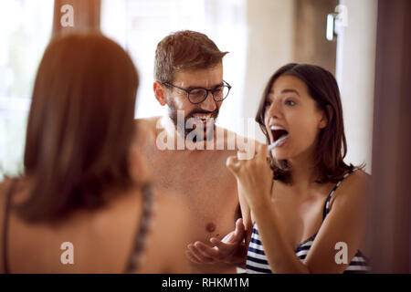 Happy couple brushing their teeth in the bathroom. - Stock Photo