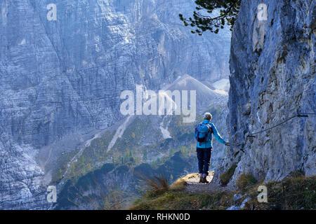 Walker on narrow path in the Sorapis Group, Dolomites, Belluno, Veneto, Italy - Stock Photo