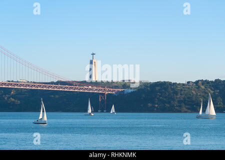 Sailboats with white sails on the Tagus River, 25 of April (25 de abril) Bridge, Christ the king elevator tower in the background, Lisbon, Portugal - Stock Photo