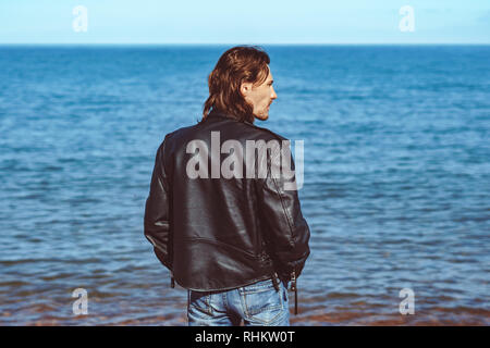 Back of male backpacker standing at the edge of coastline beach enjoying leisure time - Stock Photo