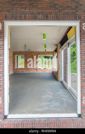 Look through at new house with concrete floor inside - Stock Photo