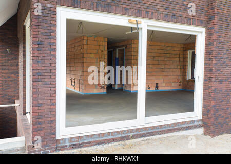 Facade of new-built house with concrete floor inside - Stock Photo