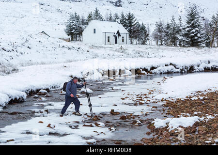 Photographer with tripod and camera crossing River Coupall after photographing Lagangarbh Cottage Hut at Glencoe, Highlands, Scotland in Winter - Stock Photo