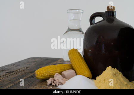 A clay half gallon jug with cob stopper and the ingredients for making moonshine corn liquor on a rustic wooden table - Stock Photo