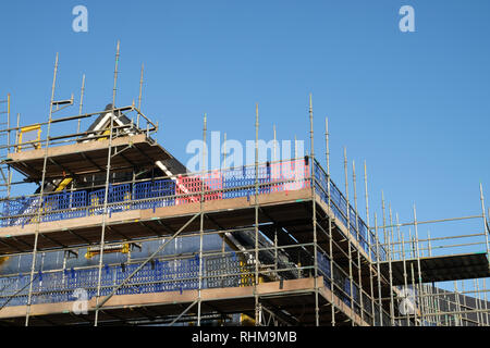 scaffolding covering a house under construction - Stock Photo
