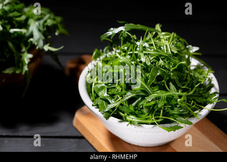 Fresh rucola in the wood bowl full of rocket salad leaves over the black background, selective focus - Stock Photo