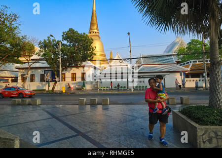The large golden stupa of Wat Boworniwet, Bangkok, Thailand, seen from Banglamphoo Square, a Thai father with his child in the foregroudn - Stock Photo