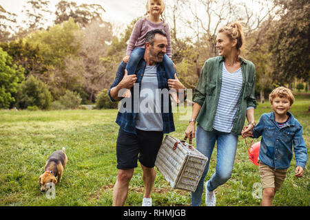 Happy family with dog walking towards the picnic spot in the garden. Man carrying his daughter on shoulders with woman holding son hand and carrying a