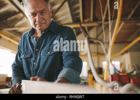 Senior carpenter measures wood, checking it for straightness. Mature male carpenter preparing furniture in his workshop. - Stock Photo