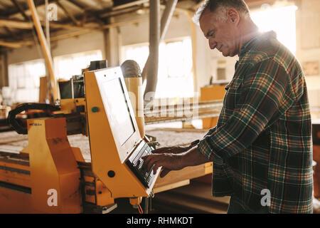 Senior male carpenter programming a cnc wood working machine in workshop. Mature man prepares a computer program for CNC machine at carpentry workshop