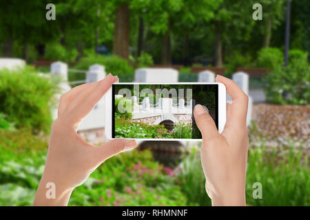 A man is making a photo of bridge over river in the Bernardine Garden in Vilnius on a mobile phone - Stock Photo
