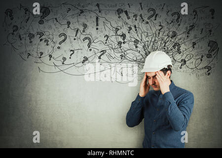 Stressed engineer holding arms to head eyes closed feeling exhausted. Headache, anxiety and health problems as sketch mess in his head. - Stock Photo