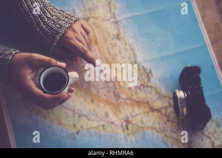 Dark tones travel wanderlust image concept with top view of woman hands looking and pointing on the next trip paper map - coffee and camera ready to s - Stock Photo