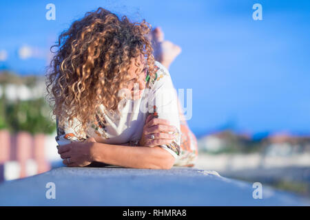 Relaxed lay down lady enjoying the day - focus on face - middle age woman in outdoor leisure activity - cold tones image - vacation concept - Stock Photo