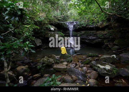 Woman in yellow rain jacket sitting on a rock by a natural poll under waterfall in the rainforest, Ishigaki, Japan - Stock Photo