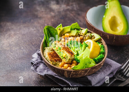 Vegan lunch in a coconut bowl: green burgers with salad and chickpeas. Healthy vegan food concept. - Stock Photo