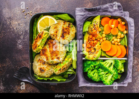 Healthy meal prep containers with green burgers, broccoli, chickpeas and salad on dark background. - Stock Photo