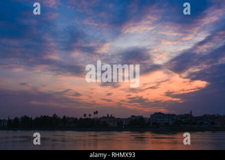 Sunset over Lake or river. Colorful pastel pink and red clouds with Blue sky abstract background and River, clouds and city sillhouette at sunset. - Stock Photo