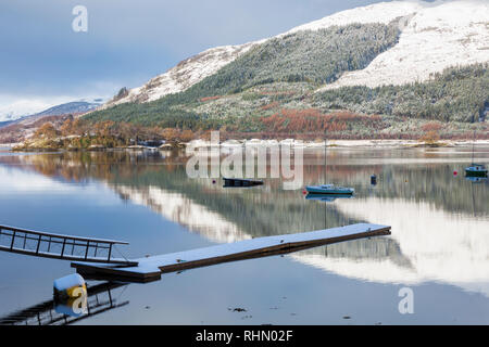 Reflections in Loch Leven with jetty and boats on a cold winter morning from Glencoe Village, Highlands, Scotland - Stock Photo