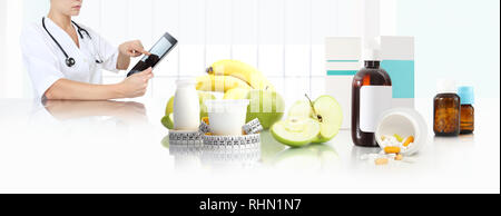 dietitian nutritionist doctor prescribes prescription by consulting the digital tablet at the desk office with fruits, yogurt, tape meter and suppleme - Stock Photo