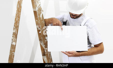 painter man with ladder showing blank white placard, copy space template - Stock Photo