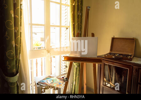Painting with oleo, materials ready to paint next to bright window on elegant room of home. Space to art work in home. - Stock Photo