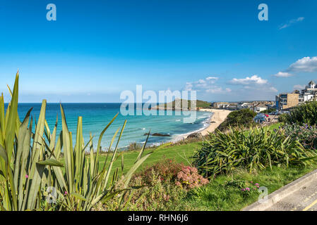Looking across Porthmeor beach towards The Island from Beach road St.ives Cornwall UK Europe on a beautiful warm summer day with blue sky and sea - Stock Photo
