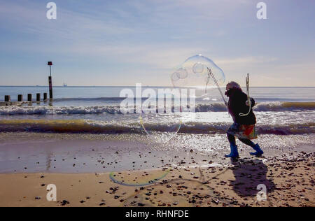 Bournemouth, UK. Sunday 3rd February 2019. A lady makes large bubbles on the beach in Bournemouth in Dorset, on a sunny winters day. Credit: Thomas Faull/Alamy Live News - Stock Photo