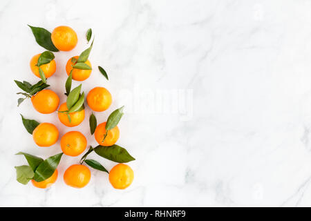 Arrangement of Clementines with leaves on white marble background with lots of copy space. Top view. - Stock Photo