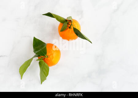 Top view of two Clementines with leaves on white marble background with copy space. - Stock Photo