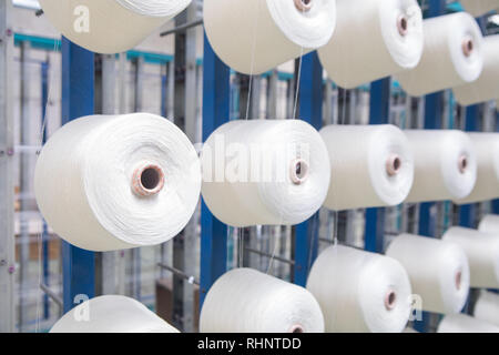 Group of bobbin thread cones on a warping machine in a textile mill. Yarn ball making in a textile factory. Textile industry - yarn spools on spinning - Stock Photo