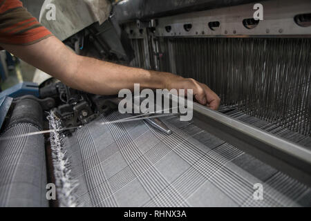 Hand on weaving loom machine. A loom machine for clothing or woven label. Weaving machine for garment industry. Weaving loom in textile factory. - Stock Photo