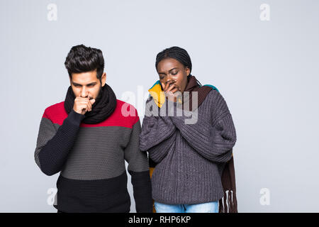 Young interracial couple african girl indian guy in gray sweaters, scarves together isolated on grey wall background. Healthy lifestyle, ill sick dise - Stock Photo